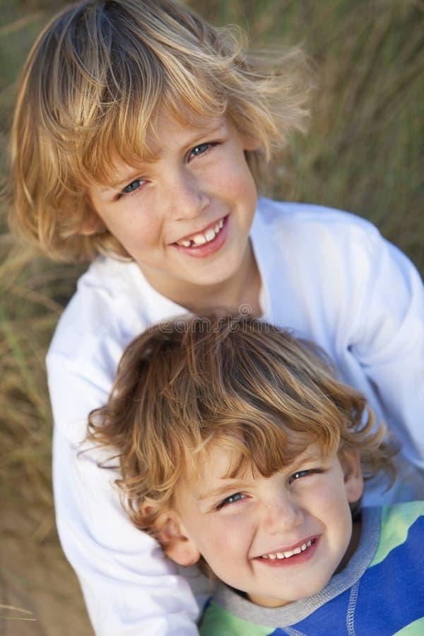 Dos niños pequeños, hermanos, en una playa asoleada imagen de archivo libre de regalías