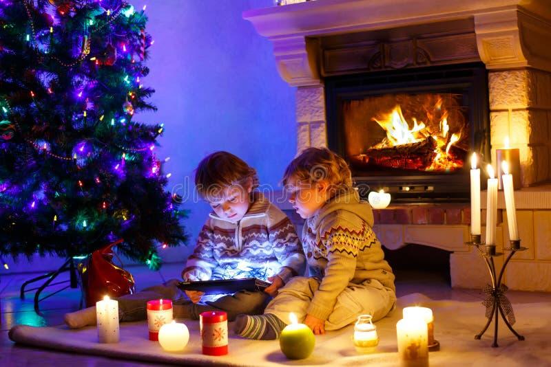 Dos niños pequeños lindos, gemelos rubios que juegan con el nuevo regalo de la tableta Familia que celebra día de fiesta de la Na fotografía de archivo