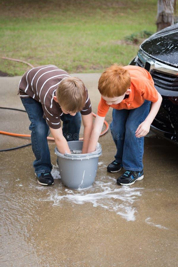 Dos niños pequeños que ayudan a lavado el coche imagenes de archivo