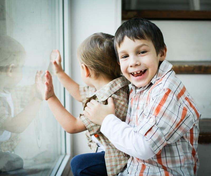 Dos niños pequeños que juegan cerca de la ventana fotografía de archivo libre de regalías
