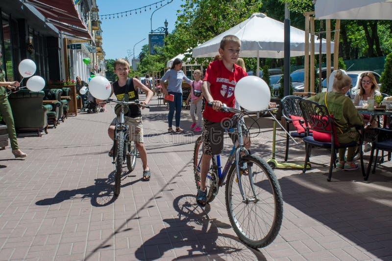 Dos niños pequeños que montan las bicicletas con los baloons durante día de la protección de los niños imagenes de archivo