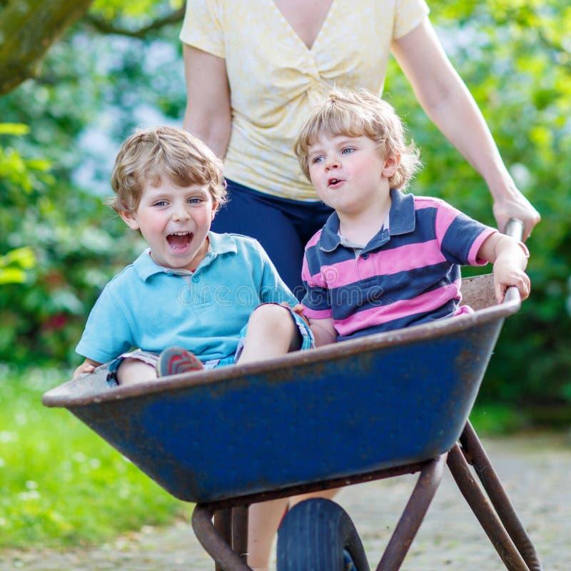 Dos niños pequeños que se divierten en una carretilla que empuja por la madre fotos de archivo