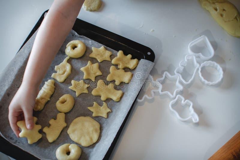 Dos niños pusieron las galletas en un molde para el horno Postres hechos en casa La visi?n desde la tapa imágenes de archivo libres de regalías