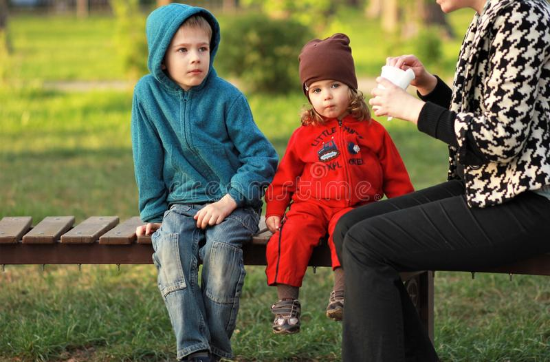 Dos niños que almuerzan su al aire libre en el parque fotografía de archivo