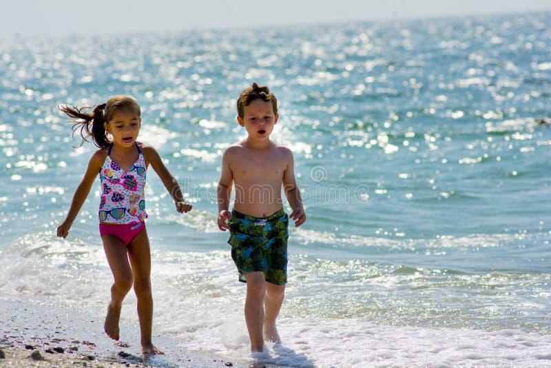 Dos niños que corren en la playa imagen de archivo