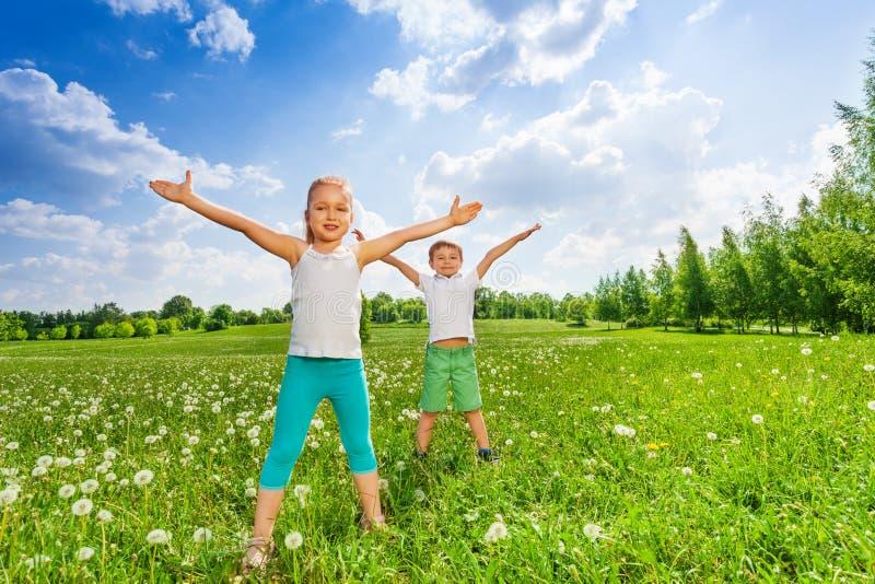 Dos niños que hacen la gimnasia al aire libre en la hierba fotos de archivo libres de regalías