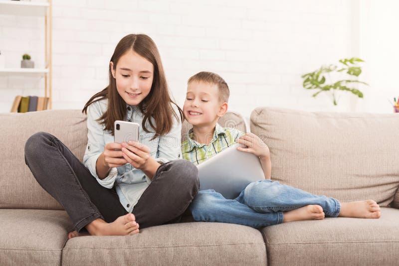 Dos niños que juegan en el artilugio en el sofá en casa imagenes de archivo
