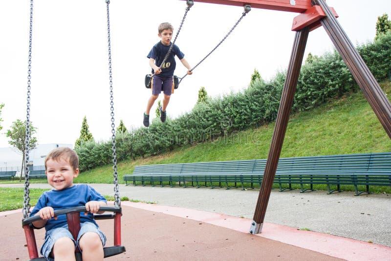 Dos niños que juegan en el oscilación fotografía de archivo