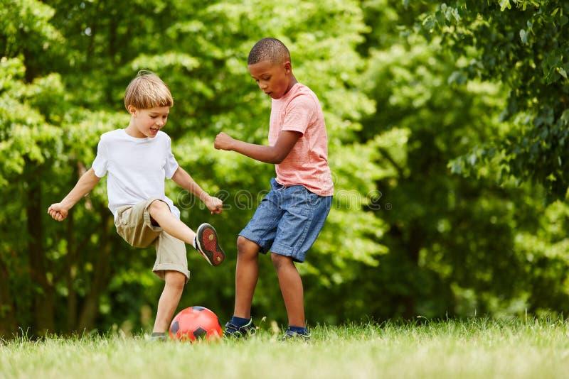 Dos niños que juegan a fútbol fotografía de archivo
