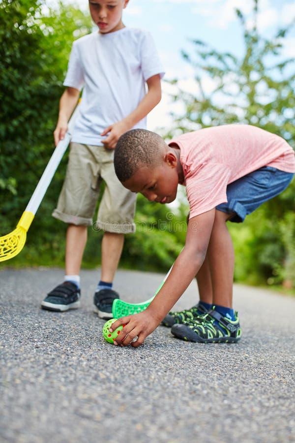 Dos niños que juegan a hockey de la calle foto de archivo