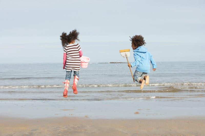Dos niños que juegan por la playa del invierno de Sea On imágenes de archivo libres de regalías