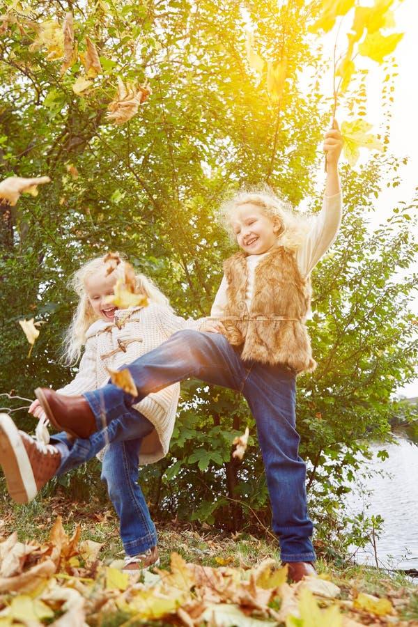 Dos niños que juegan y que bailan en otoño foto de archivo
