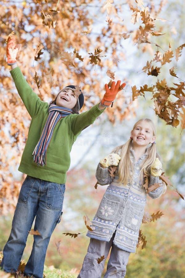 Dos niños que lanzan las hojas en el aire imagen de archivo libre de regalías