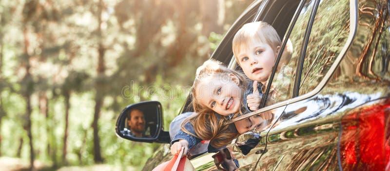 Dos niños que miran hacia fuera la ventana mientras que su padre que conduce un coche Viaje por carretera de la familia fotografía de archivo