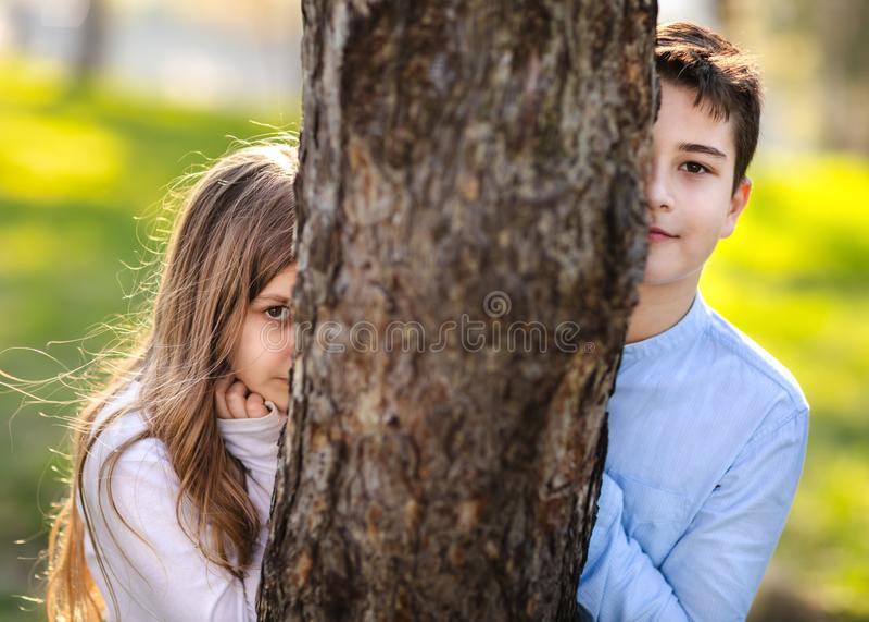 Dos niños que ocultan detrás del árbol Chica joven y muchacho que juegan alrededor del árbol en parque Retratos de dos niños en e fotos de archivo libres de regalías