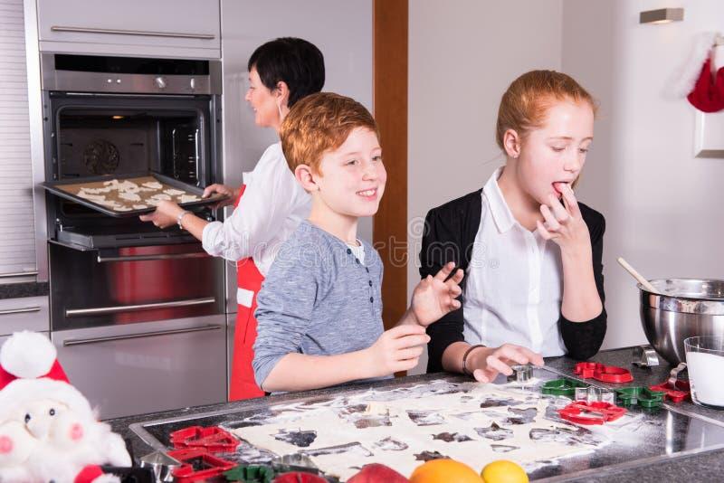 Dos niños que preparan la panadería de la Navidad - la madre introduce las galletas imagen de archivo libre de regalías