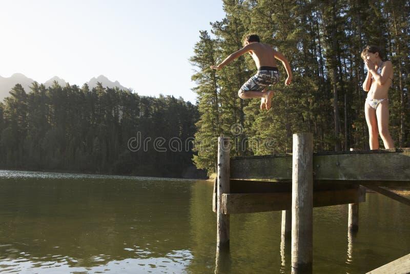 Dos niños que saltan del embarcadero en el lago fotos de archivo