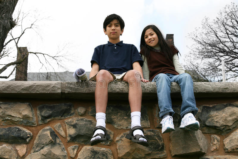 Dos niños que se sientan en la repisa de la roca imagen de archivo