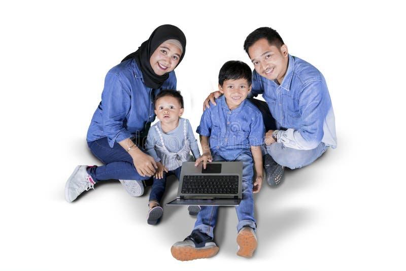 Dos niños que usan un ordenador portátil con sus padres fotos de archivo