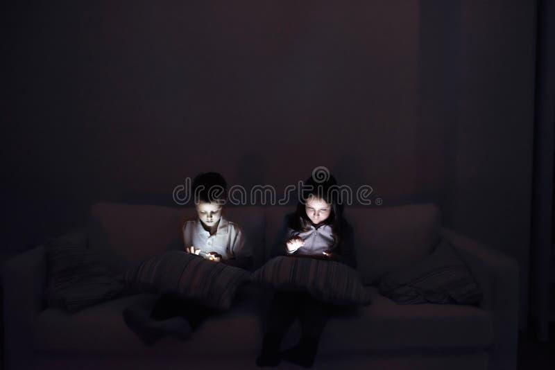 Dos niños, sentándose en un oscuro, jugando con los artilugios imágenes de archivo libres de regalías