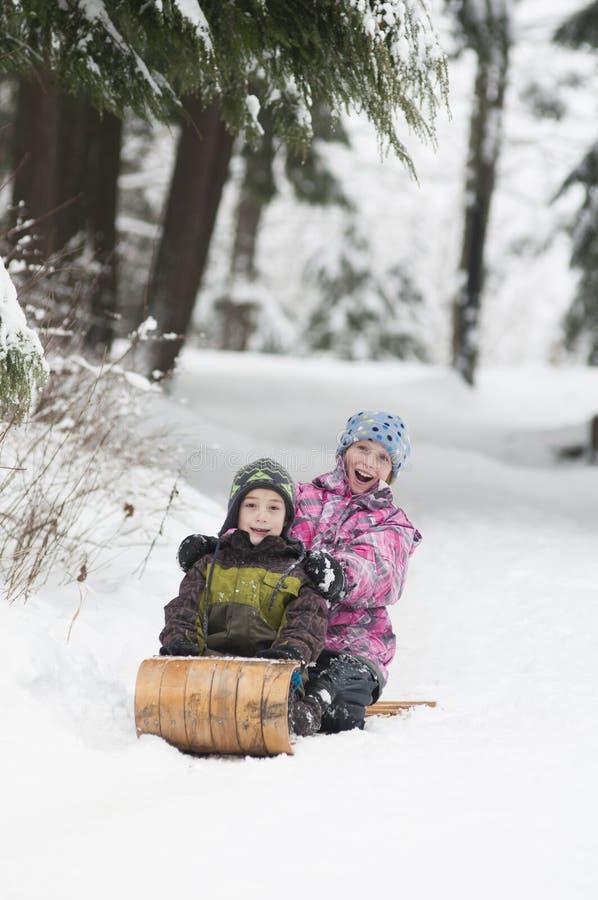 Dos niños tobogganing imagenes de archivo