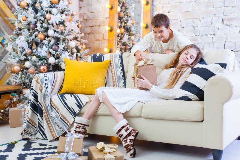Dos niños un muchacho y una muchacha en un árbol de navidad en un sofá con los regalos En colores claros dé los presentes el uno  fotografía de archivo libre de regalías