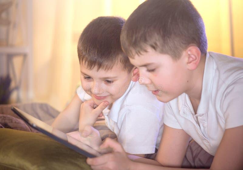 Dos niños usando la PC de la tableta en dormitorio fotos de archivo