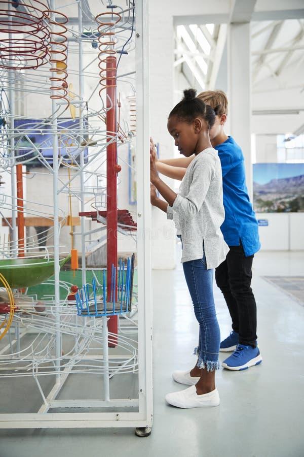 Dos niños y mirada de un objeto expuesto de la ciencia, vertical imagenes de archivo