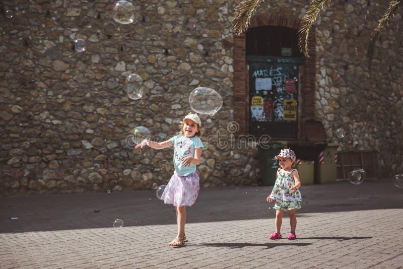 Dos ni?as bonitas est?n jugando con las burbujas grandes en calle en d?a de verano fotos de archivo libres de regalías