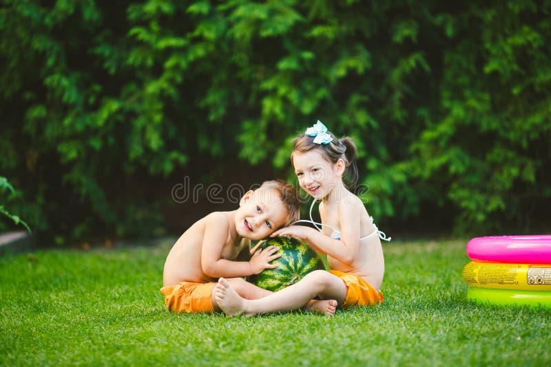 Dos ni?os, hermano cauc?sico y hermana, sent?ndose en hierba verde en el patio trasero de la casa y abrazando la sand?a dulce sab fotografía de archivo libre de regalías