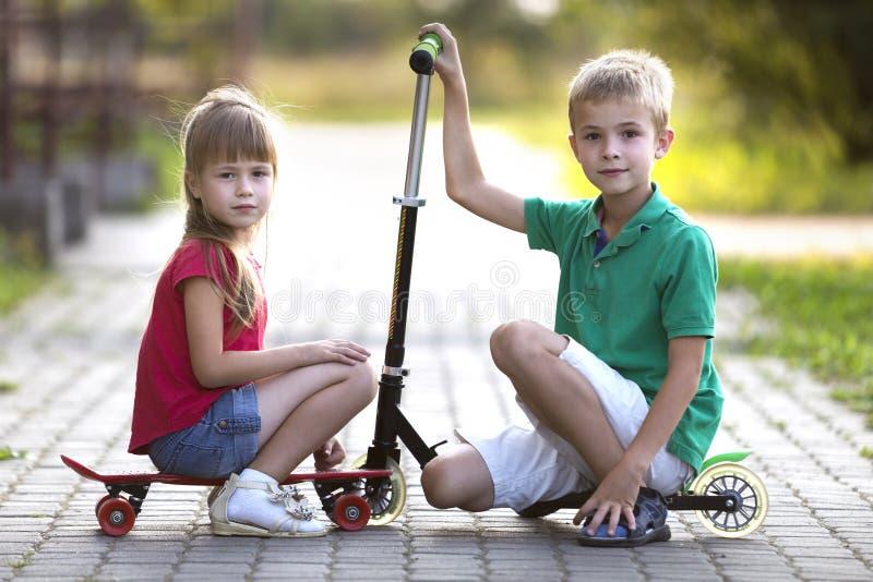 Dos ni?os jovenes sonrientes divertidos felices lindos, hermano y hermana, presentando para la c?mara, el muchacho con la vespa y fotos de archivo libres de regalías