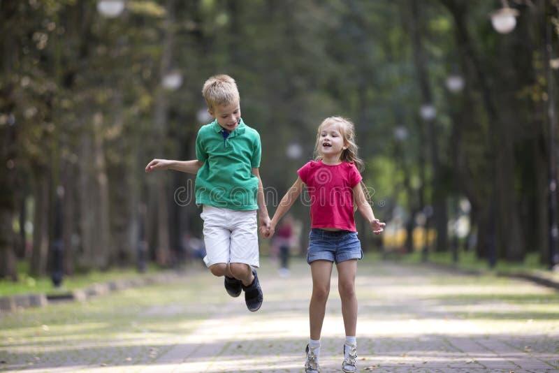 Dos ni?os sonrientes divertidos jovenes lindos, muchacha y muchacho, hermano y hermana, saltando y divirti?ndose en el callej?n s foto de archivo libre de regalías