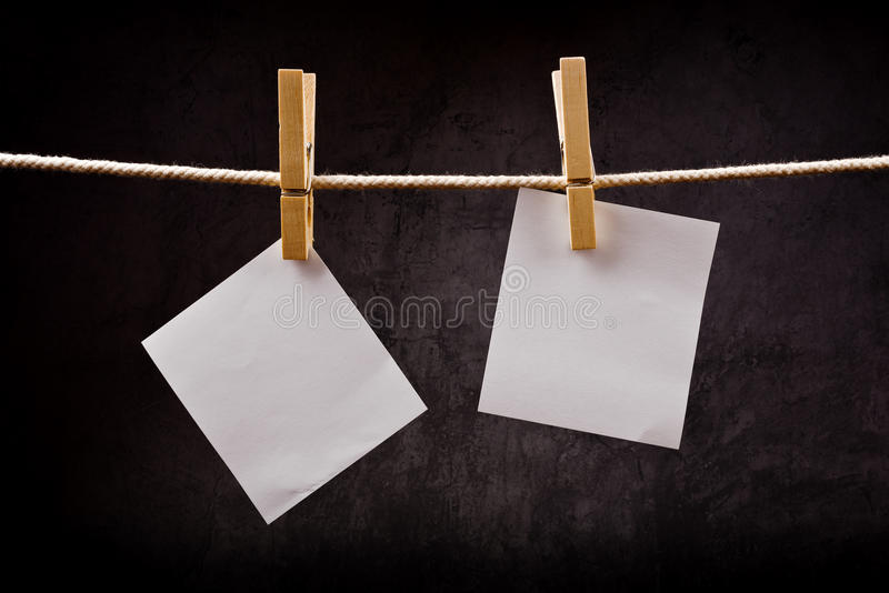 Dos notas del papel en blanco que cuelgan en cuerda con los pernos de ropa imágenes de archivo libres de regalías