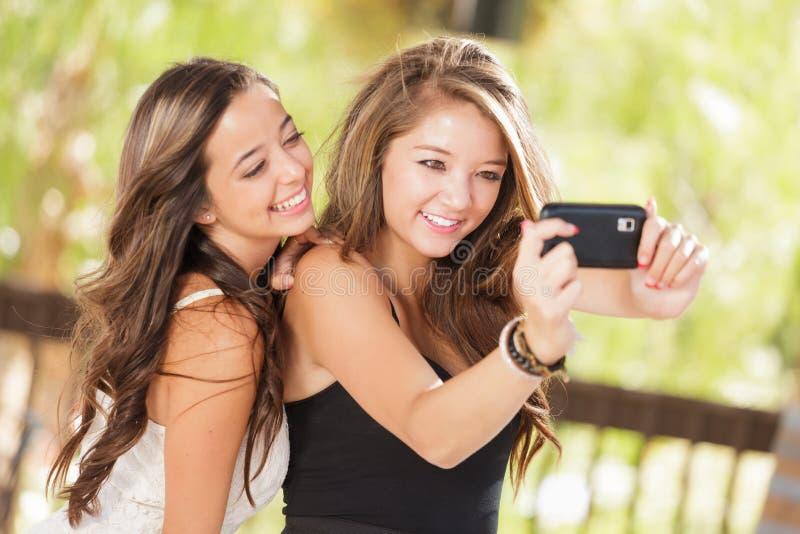 Dos novias atractivas de la raza mixta que usan su célula elegante Pho fotografía de archivo