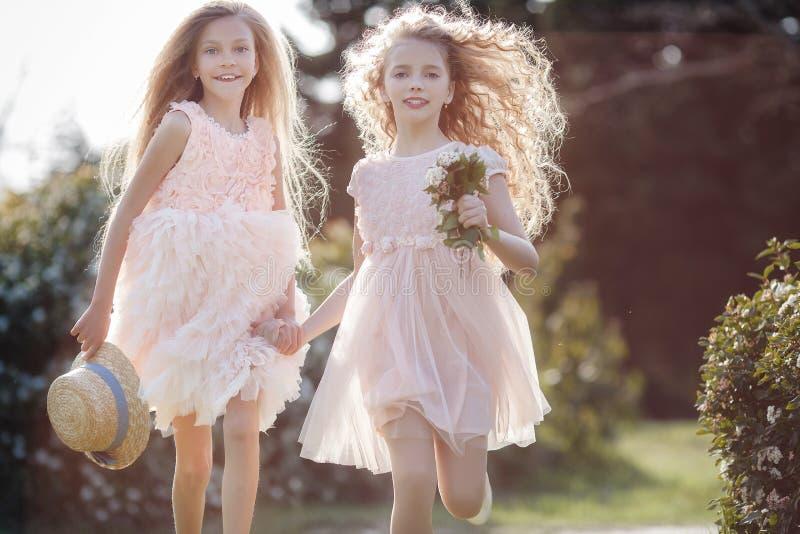 Dos novias corren a través del parque de la primavera que lleva a cabo las manos foto de archivo libre de regalías