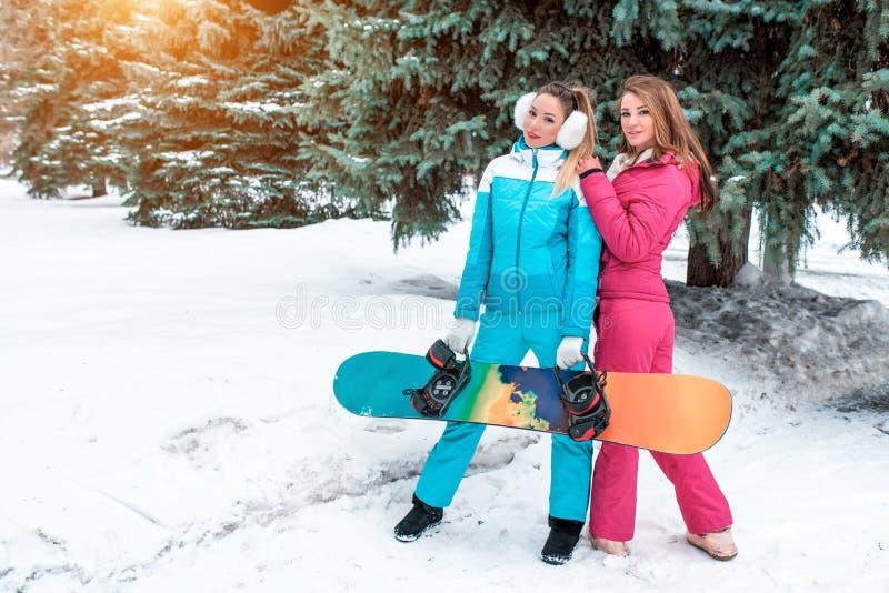 Dos novias de las muchachas en las snowboard, presentando en el fondo de árboles de navidad verdes En manos de un tablero de la s foto de archivo
