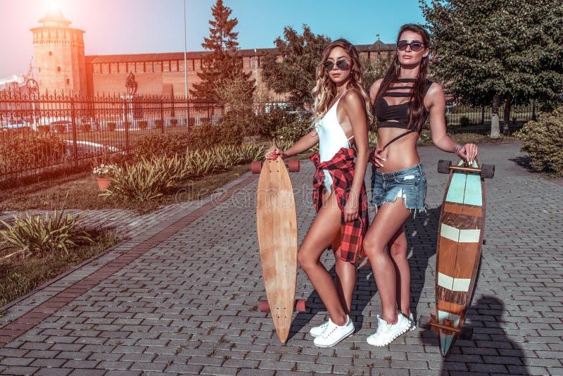 Dos novias de las muchachas, fondo permanente de la figura de los árboles, del monopatín, hermosa y bronceado de la ciudad Mejore foto de archivo libre de regalías
