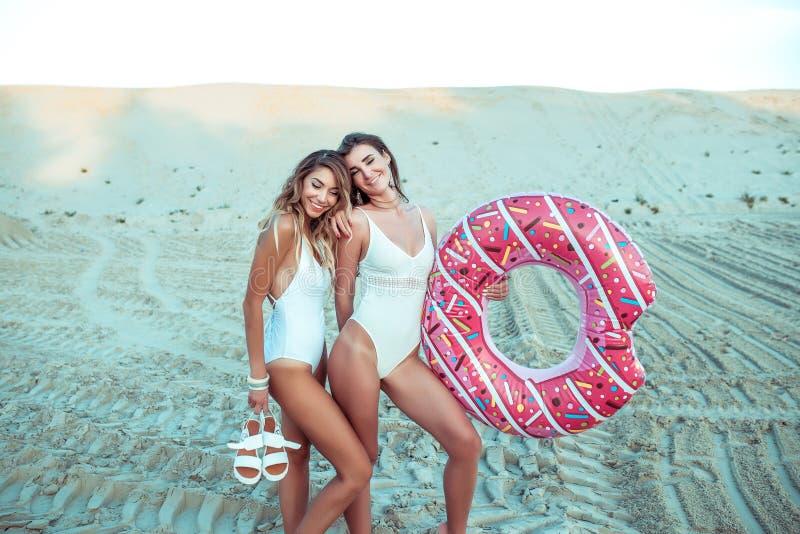 Dos novias de las muchachas que colocan la arena con el c?rculo inflable, las mujeres hermosas varan el mono blanco Mar de los d? imágenes de archivo libres de regalías
