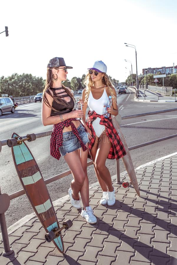 Dos novias de las muchachas que sostienen las botellas de agua, coches del monopatín del camino del fondo, figuras bronceadas her fotos de archivo libres de regalías
