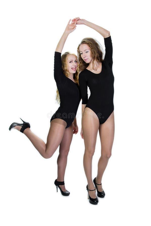 Dos novias en negro se divierten el traje de baño en un fondo blanco fotos de archivo libres de regalías