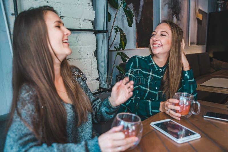 Dos novias que hablan en rato del café para beber un té Encuentro imágenes de archivo libres de regalías
