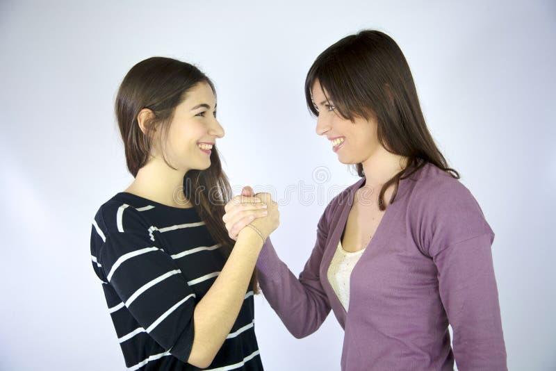 Dos novias que llevan a cabo la risa sonriente de las manos fotos de archivo