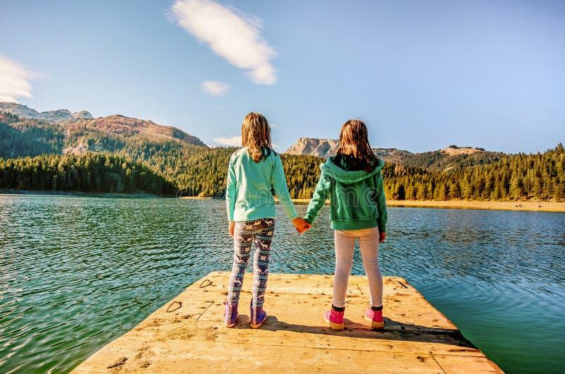 Dos novias que llevan a cabo las manos y que admiran el lago negro en el Du foto de archivo libre de regalías