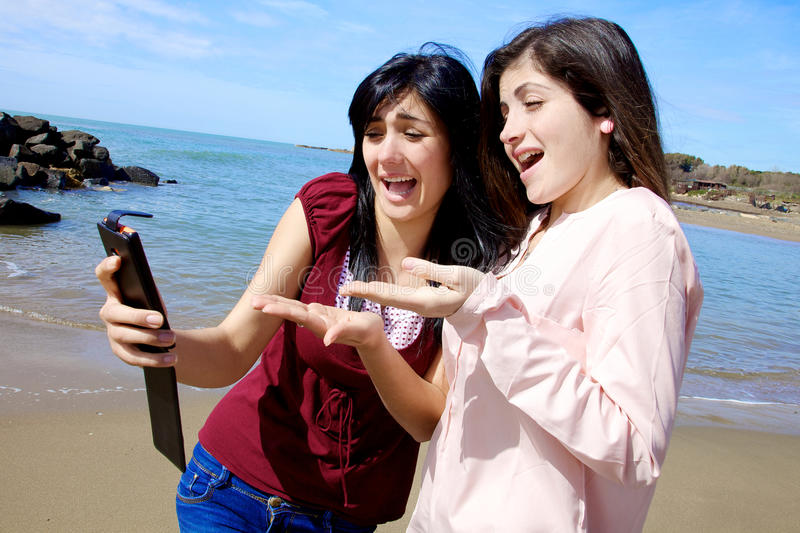 Dos novias que miraban el selfie han hecho infeliz fotos de archivo