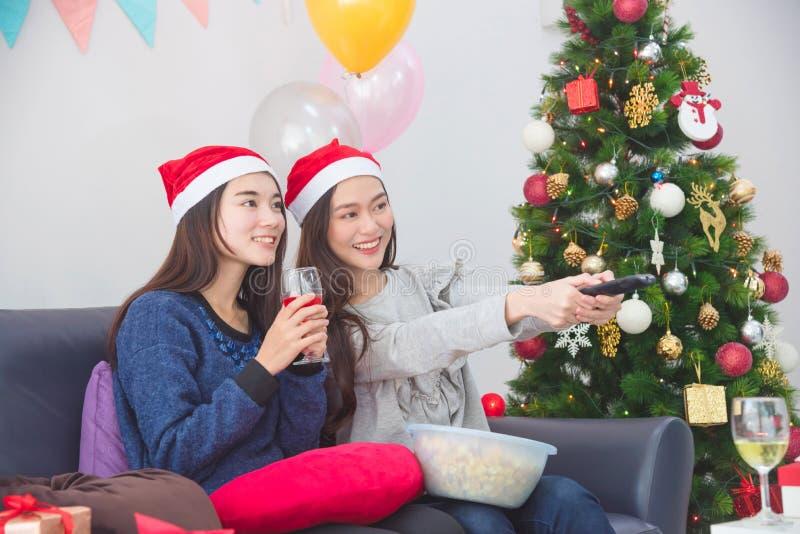 Dos novias que pasan día de fiesta de la Navidad, comiendo las palomitas y mirando película en sala de estar foto de archivo libre de regalías
