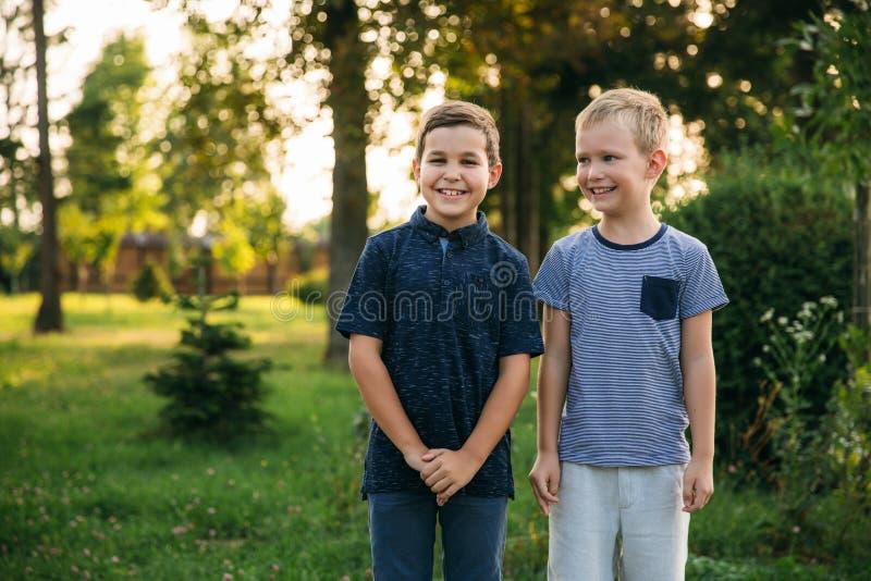 Dos novios de los niños que caminan en el parque en un día de verano soleado hermanos imagen de archivo libre de regalías