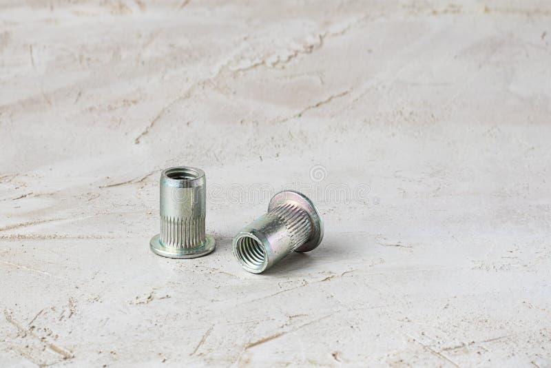 Dos nueces grises del río del metal para el hilo interno duro para las unidades finas en parte izquierda de cemento texturizado t fotografía de archivo libre de regalías