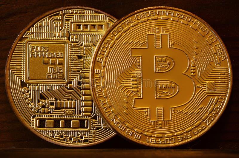 Dos nuevos bitcoins físicos de oro mienten en el backgound de madera oscuro, cierre para arriba Foto de alta resolución Concep de foto de archivo libre de regalías
