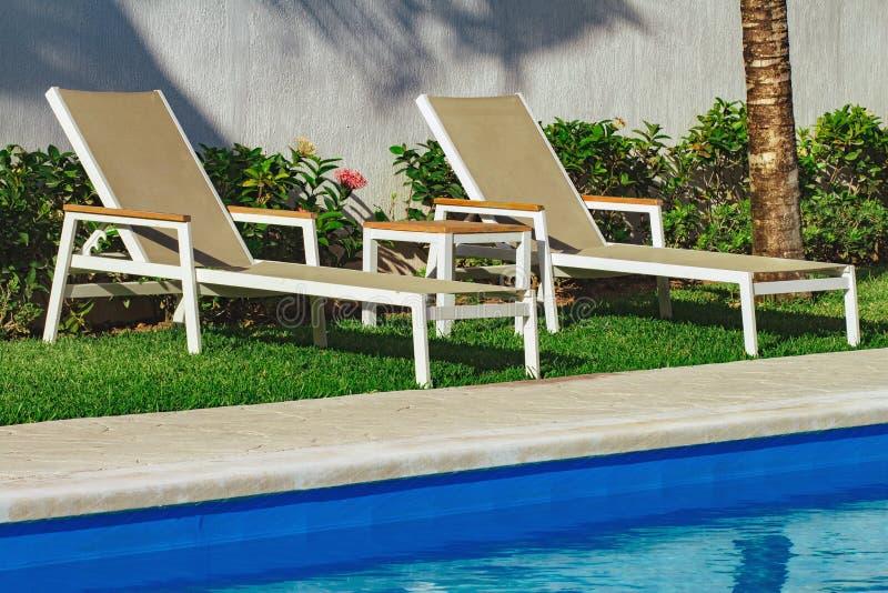 Dos ociosos del sol por la piscina imágenes de archivo libres de regalías
