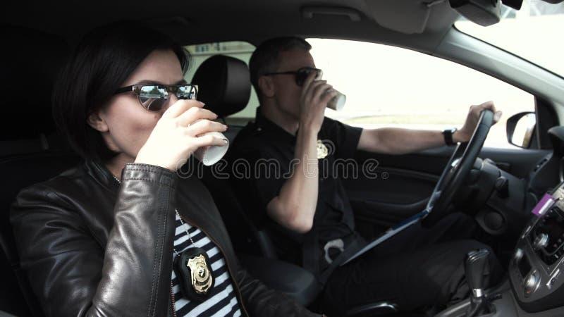 Dos oficiales de policía que se sientan en coche durante rotura fotos de archivo